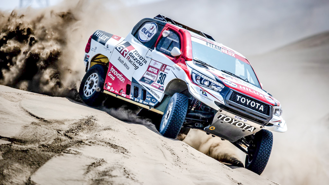 Image of Dakar race car driving over a sand dune